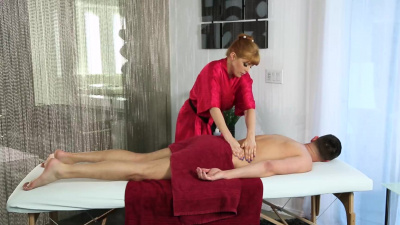 Redhead masseuse massages client's dick with her mouth and pussy